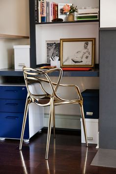 A sleek gold Kartell chair elevates a minimal corner work space.