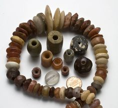 """Neolithic stone beads, these were ground or knapped by hand and drilled with a bow drill or similar; the perforations were drilled from both ends to ensure the bead would not break during the drilling process. This can be somewhat seen in the transparent quartz bead."""