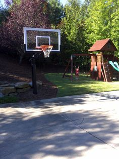 There is a Pro Dunk Gold Basketball System and its post is surrounded by the mulches. Behind the hoop there's the retaining wall. On the right, in the background you can see a young girl swinging at her playground area.