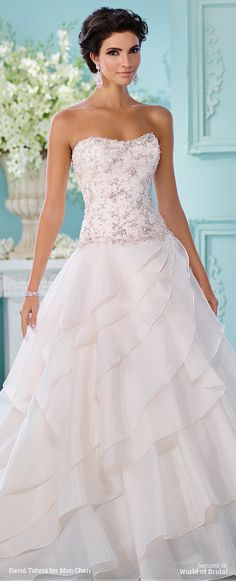 Strapless organza over satin full A-line gown softly curved neckline, delicately hand-beaded drop waist bodice with back covered buttons, asymmetrically tiered circular cut skirt, chapel length train, detachable spaghetti and halter straps included.