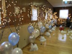 I made 'trees' by using tree branches and setting them in concrete in large green bean or coffee cans. Then covered with a snow blanket and added lights for my Prom Birthday party. The balloons are tied to blue disco ball Christmas ornaments as weights. Just a little more sparkle