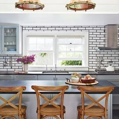 This Long Island kitchen gets an infusion of natural elements from the copper light fixtures and wooden bar stools. | Coastalliving.com