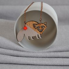 Origami Raccoon Necklace from artysmartyshop.com This origami style Necklace is made from wood and then carefully hand painted in pastel colors and finished with a durable varnish. The chain is an vintage style antiqued copper with a lobster clasp, glass bead and 'artysmarty' rabbit tag.   #handmade #jewelery #fashion