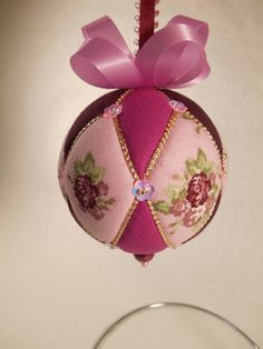 "Ornament is made using a polystyrene ball covered in beautiful purple and pink flowers. Solid fabric is light and dark purples. Also used are champagne-colored cord, and pink iridescent flower-shaped sequins, finished with pale lavender ribbon.  Would make a great gift for a bridesmaid or matron of honor  Ball is about 3 inches tall.  Ornament is made using the Japanese-style called Kimekomi that generally means ""to tuck."" A design is drawn on a polystyrene ball, which is cut with a craft…"
