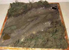 Un petit coin de terre :  terrain = pâte à modeler qui durcit à l'air ; herbe Héki en rouleau découpée aux formes ; sol = terre à décor (déco d'intérieur, Casto) + gravier + colle + enduit, le tout fixé au pinceau ;  herbes hautes = filasse de plombier ; peinture à l'aérographe => des marrons pour les parties terre, des verts pour les herbes, puis drybrush de différents jaunes sur herbes et terre ; quelques flaques d'eau = résine d'inclusion + un marron Vallejo + 1 goutte de noir mêlés dans…