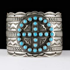 "This is a Sunshine Reeves Heavy gauge Sterling Silver Bracelet, The cuff shows deep stampwork which is flawlessly executed, featuring geometric designs commonly found in old Navajo rug weaving. Crowning the cuff is a sacred ""Medicine Wheel"", pointing to the Four winds, with a cluster of  Sleeping Beauty Turquoise stones."