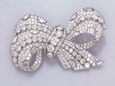 AN IMPRESSIVE DIAMOND RIBBON BOW BROOCH   Designed as alternating bands of collet and pavé-set diamonds, enhanced by baguette-cuts (one small diamond deficient), circa 1935