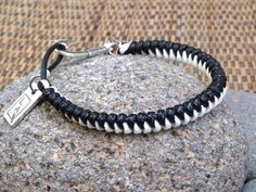 Thin black and white braided men's bracelet from laQ with a fish hook as clasp.
