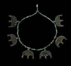 Viking Necklace with Lunate Pendants, 9th-11th Century ADRestrung with rolled sheet bronze beads and 6 large (50mm) lunate pendants with ring-and-dot motifs.