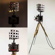 A Vintage Polaroid Camera converted into a Lamp. The Camera is mounted on a wooden Tripod with Steel Rod legs. The Camera is fitted with a Lamp Shade made with Vintage Photo Slides and illuminated from within with a Light Bulb.