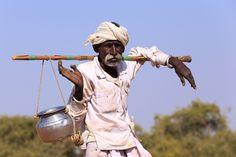 Um pastor Rabari idoso e seu jarro de água na icônica vara que leva sobre o ombro. Os Rabari são uma casta tribal indiana de pastores nômades de gado e camelos que vivem no noroeste da Índia, principalmente nos estados de Gujarat e Rajastão, e alguns estados no Paquistão, especialmente na região do deserto de Sindh.  Fotografia: Sayid Budhi (DocBudie) no Flickr.