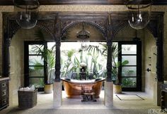 In this Martyn Lawrence Bullard-designed Malibu home, the copper tub in the master bath is by Waterworks, and the hanging lanterns, teak facade, and carved marble panel are Indian. Tour the rest of the home.   - ELLEDecor.com