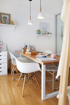Cómo decorar un monoambiente chico: mesa liviana con base de hierro y tapa de madera clara, sillas Bertoia y sillón tipo Eames de fibra de vidrio moldeado y patas de madera.