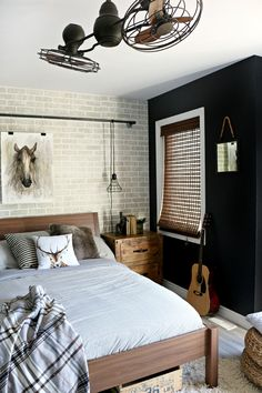 Industrial Teen Bedroom Makeover | Leon's Furniture// We opted to line the focal wall with a faux brick panel and added an industrial pipe across the top to hold the hanging cage lights and art work.|Home Decor| Teen Boy Bedroom| Bedroom Makeover