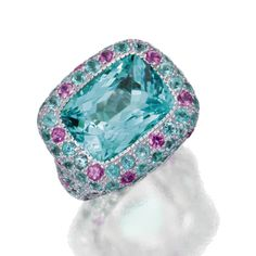 PARAÍBA TOURMALINE AND PINK SAPPHIRE RING, MICHELE DELLA VALLE The mixed-cut paraíba tourmaline weighing9.04 carats, framed by round pink sapphires and round paraíba tourmalines, mounted in 18 karat white gold, size 6¾, maker's mark, numbered 10835.