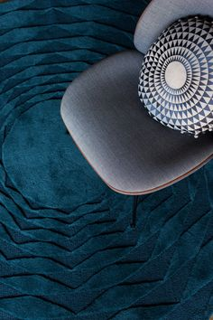 Graphic Teal Polygon Rug and Concentric Cushion with pompoms both by Niki Jones, with Gubi Beetle Chair. Round rug living room ideas. niki-jones.co.uk