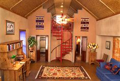 I helped build a straw bale house when I was in Arizona.  It is an awesome and economical building material, cool in the summer and warm in the winter.  You can build in benches and display nooks... even your bed platform!  I like this site as a woman built her own house with a little help from her friends for about $50,000.