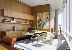 """Many of the penthouse's design elements, including the pocket doors throughout and the African teak cabinetry in Sarah's study, were created by Emily Summers's architectural team. The painting """"One More Day 4"""" is by Hungarian artist Zsolt Bodoni-Dombi 