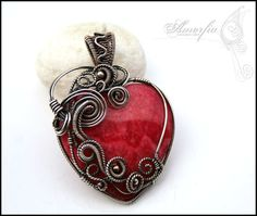 "A heart of Aphrodite. ""Beautiful rhodochrosite (?) heart pendant bead is is set in a sterling silver wire frame which is tightly wire wrapped with fine silver wire. Pendant is decorated with sterling silver round beads and romantic swirls that follow the shape of the stone. I oxidized and polished it. Pendant measures 6 x 4 cm (2.36 x 1.57'')."" Visit: jewelrylessons.com"