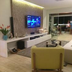 Sala de Estar e de televisão com estilo bem moderno com móvel em laca branca brilhosa e piso em porcelanato parecendo com travertino. O painel de tv com o uso do revestimento de madeira trouxe aconchego.