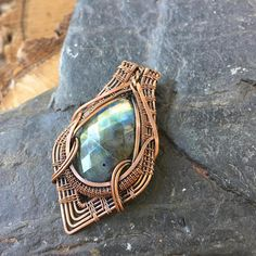 This pendant features a beautiful faceted labradorite cabochon that flashes golden and blue depending on how the light hits it. This wire wrap is constructed of raw copper that has been antiqued and polished to highlight the details of the wire work. This labradorite wire wrap