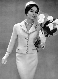 1959 Sondra Peterson in white wool suit with blue and white check trim, featuring a shorter jacket, by Pierre Balmain, pillbox by Jean Barthet, photo by Pottier,