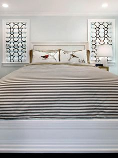Simple Style  A simple, white headboard with a molding surround keeps the focus on the prints, patterns and stripes of the bedding and window treatments. Design by Natalie Umbert.