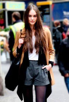 Street style look blusa branca, shorts preto e casaco caramelo.