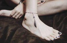 tatouage discret, dessin en encre imitation bracelet de cheville avec plume, manucure noire sur ongles longs
