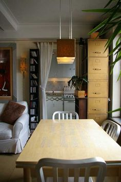 Dining area with draped-off kitchen option. Also like the use of the narrow bookshelf and tall filing cabinet on either side of the doors.