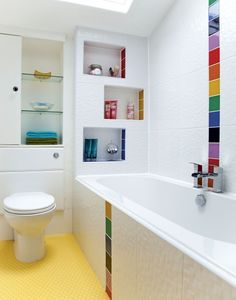 Inset shelving in this rainbow-themed bathroom adds to the effect by injecting colour in a subtle way at the same time as creating a practical storage area