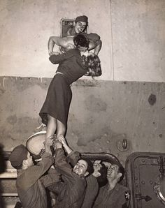 Arlene Dietrich passionately kisses a soldier returning home from WWII through a porthole on the Monticello as other soldiers lift her up Photo by Irving Haberman.(1945)