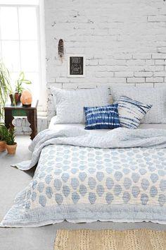 chambre bohème avec mur de brique blanche, couette en blanc à motifs bleus et plantes vertes comme accent