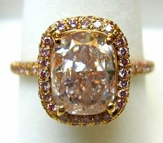 Gorgeous ring with diamonds. The Queen of Sheba would be envious of whoever owned this outstanding display of very rare pink diamonds.  Extremely well crafted ring with even rarer round cut vivid pink diamonds surrounding the large pink cushion diamond and lining the band.  Almost an Art Deco style that never goes out of style.