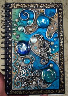 I covered it with a sheet of black Fimo, cut holes in the clay where the glass gems si. Polymer clay on acrylic tile Diy Fimo, Polymer Clay Kunst, Polymer Clay Crafts, Journal Covers, Art Journal Pages, Art Journals, Blank Journal, Kunstjournal Inspiration, Art Journal Inspiration