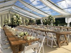 Beautiful clear roof wedding marquee with bespoke ivory roof overlay linings. Rustic tables and white fold out wedding chairs.