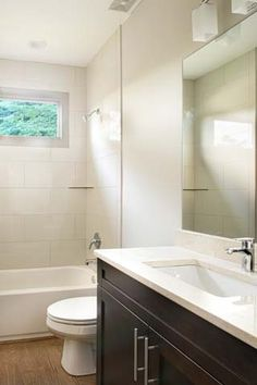 This modern style bathroom features an espresso vanity with rectangular under mount sink, quartz countertop and Grohe single level faucet, porcelain tub/shower surround and modern design lighting.