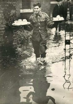 British soldier brings tea to comrades working to repair banks of River Ravensbourne which flooded South London, 1939