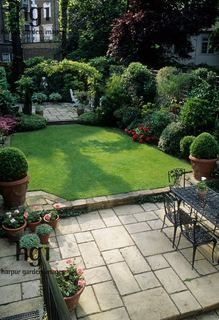 Harpur Garden Images :: CM200 Small formal town garden with paved patio, dining table and chairs, lawn, containers, borders, arch dividing separate patio at far end of garden. Christopher Masson, London Mrs Kalborg Jerry Harpur Please read our licence terms. All digital images must be destroyed unless otherwise agreed in writing. Photograph by: www.harpurgardenlibrary.com Contact: Harpur Garden Library 44 Roxwell Road Chelmsford Essex CM1 2NB, UK