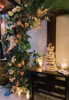 This four-tier, rose-studded naked cake seems right at home under the lush, tropical floral-and-greenery arch.