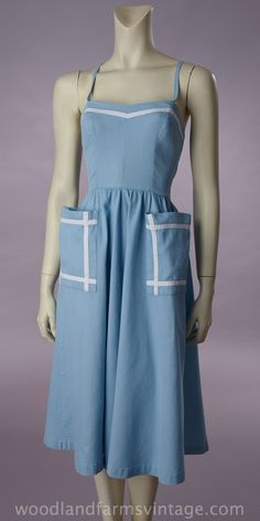 1950s blue pique cotton sundress with a double loop strap for the halter and shoulder straps. The bodice is fitted with curved bust seams running vertically. The moderately full skirt is gathered into the waistline seam. White narrow band of white pique accent the rolled edge of the neckline and on the patch pockets of the skirt.