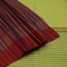This #sari is an interesting blend of many designs: It is a Half and Half Sari since the body is horizontally divided into two halves; top half in a lovely plain apple green while lower half is light stripes. It is also a #Patli Pallu Sari since the pleats portion is created with vibrant checks. A two tone rust forms an interesting contrast in the border. Stripes and bands of apple green, blue and rust form the pallu while the blouse is a simple repitition of the body. Code 420504291.