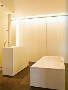 Banheiro branco e banheira retângular e piso escuro