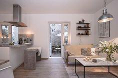 Dans cet appartement de 54m², les éléments couleur béton se marient parfaitement avec le bois du parquet et les teintes neutres des meubles. On pourrait croire que le béton est un matériau froid, il p