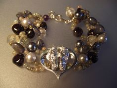 Beautiful silver heart with a cluster of gemstone beads:  Iolite, Amethyst, and pearls.  Sterling silver clasp and findings.  Handmade charms.  $95 https://www.etsy.com/shop/ForgeHillSculpture