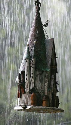 Castle-like birdhouse hanging in the rain