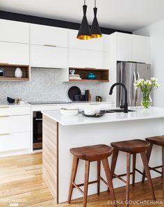 Le nouvel agencement de la cuisine permet à plus de personnes de profiter de la salle à manger en utilisant un banc encastré, en élargissant l'îlot de cuisine et en ayant plus de rangement. Les placards sur commande en blanc et le plan de travail en quartz se marient parfaitement avec du bois en noyer. Le mur en papier peint contemporain de Pierre Frey ressemble à une toile géante. Les accents en noir et blanc, le décor en bronze donnent une élégance intemporelle à l'espace.