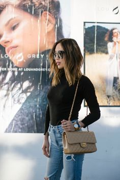 Aimee song wearing black turtle neck and light wash jeans, carrying a vintage nude chanel bag