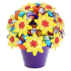 Happy Bloom Large - Brighten their day with this cheerful bloom in every colour of the rainbow! Featuring a selection of 50 delicious gourmet chocolates amongst our signature flowers, this beaming beauty is just the trick to add a smile to their dial.