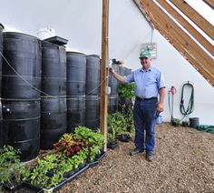 Passive solar greenhouses store sun's heat in barrels of water